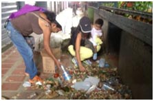 Young women picking through the garbage, looking for something to eat.